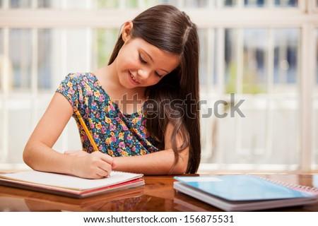 Pretty little girl enjoys learning and doing some homework