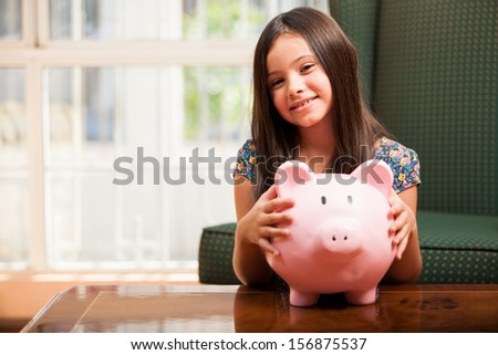 Pretty little girl holding her piggy bank and smiling in the living room