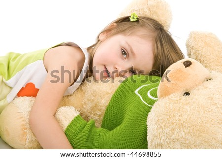 Pretty little girl hugging big bear isolated on white.