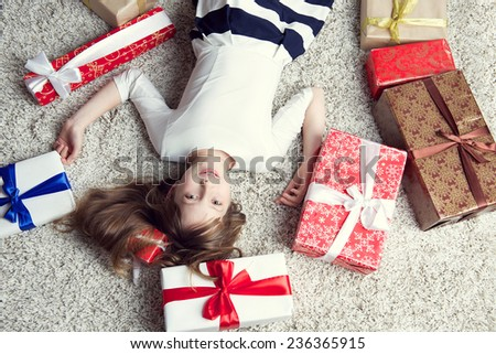 Pretty little girl in a beautiful dress lying on the carpet surrounded by gift boxes. Studio photo