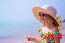 Pretty little girl in a swimsuit, sun glasses and hat relaxing on the beach near sea. Smiling cute little girl on vacation. Adorable girl in a big straw hat looks at the sea. Summer travel concept