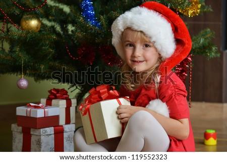 Pretty little girl  in santa cap near Cristmas tree