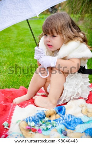 Pretty little girl is cold & hiding under umbrella in the park barefooted