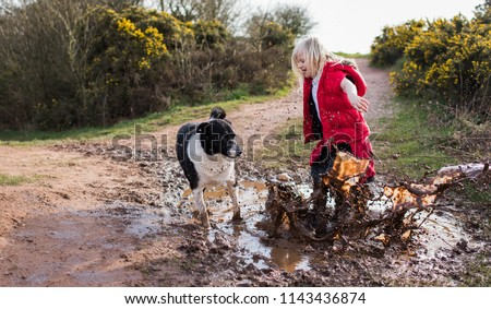 Pretty little girl jumping in very muddy puddle playing with her pet dog