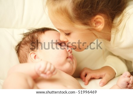 pretty little girl kissing her adorable baby brother
