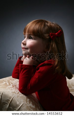 pretty little girl kneeling on couch with  chin on her hands