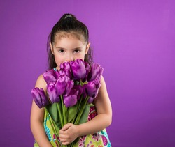 Pretty little girl  looking from behind large tulip flower bouquet isolated on purple background