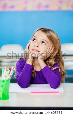 Pretty little girl looking up while sitting with head in hands in drawing class