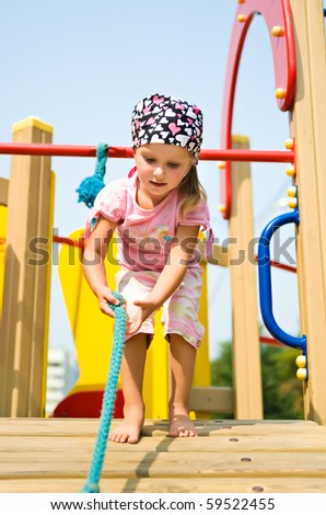 Pretty little girl on outdoor playground equipment