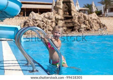 pretty little girl on the ladder of the pool