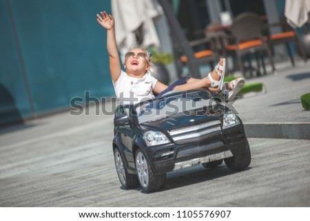 Pretty little girl outdoors. Cute child driving the toy car outside. #1105576907