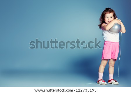 Pretty little girl over grey background.