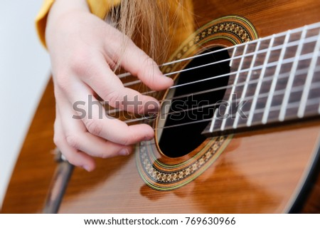Pretty little girl playing acoustic guitar