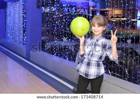 pretty little girl playing bowling