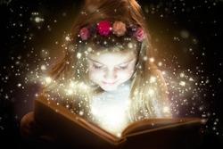 Pretty little girl reading magic book