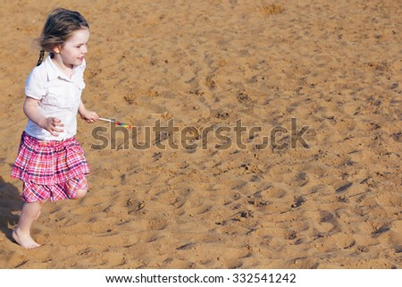 Pretty little girl runs with bright lollipop on sand at summer sunny day #332541242