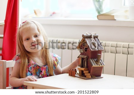 Pretty little girl sits at table with small wooden toy house and smiles