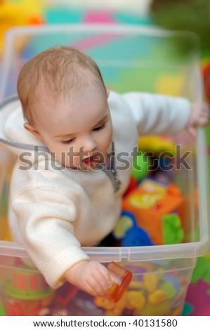 Pretty little girl sitting in a toy box