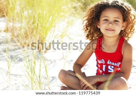 Pretty little girl sitting in the sand while playing with the tall grass near the ocean
