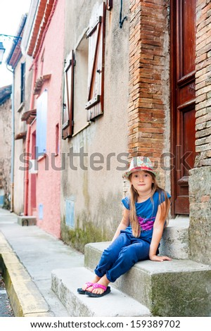 Pretty little girl sitting on a step, wearing blue pants and top, hat with flowers