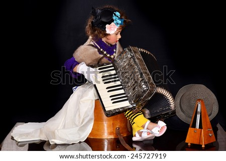 Pretty little girl sitting on a vintage hat box and plays the accordion near the metronome and old hats