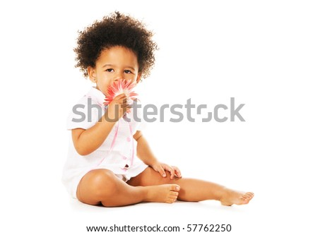 Pretty little girl smelling a flower isolated on white