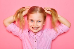 Pretty little girl standing on pink background and holding ponytails on her head.