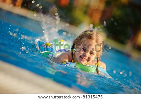 Pretty little girl swimming in outdoor pool and have a fun with a splash
