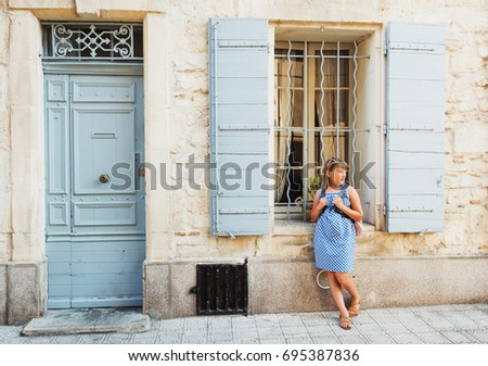 Pretty little girl tourist on the streets of Provence, Wearing blue gingham dress, sunglasses and backpack. Travel with children concept. Image taken in Arles, France