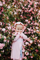 Pretty little girl wearing pink bonnet and pink dress in blossom bush of pink camelia in sunny spring day