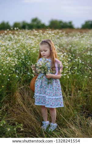 4d1be01de15 Pretty little girl with a long blond hair in a simple dress and with a  wicker