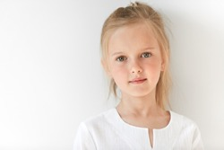 Pretty little girl with Caucasian traits looking peacfully and standing still like obedient child. She looks beautiful, attractive, nice, kind and well-mannered.