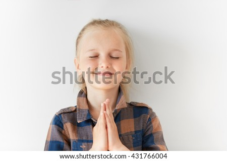 Pretty little girl with closed eyes smiling and meditating with happy face in morning light. Blond Caucasian kid putting hands together as if praying for lovely day to come or making wish for birthday