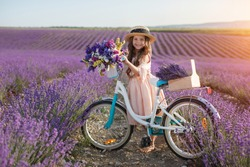 pretty little girl with flowers and straw hat having fun in lavender field. Preteen girl with bicycle.