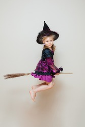 Pretty little girl with funny tricky face pretend like flying on the broom with the company of black cat on her broom stick. Kid girl wear black and purple witch costume. Halloween coming.