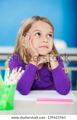 Pretty little girl with hand on chin looking away while sitting at desk in class