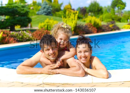 Pretty little girl with her parent in swimming pool outdoors stock photo