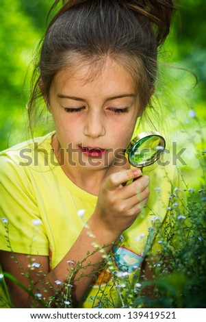 pretty little girl with magnifying glass looking at flower