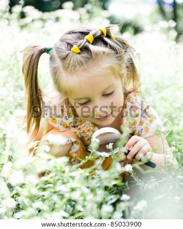 pretty little girl with magnifying glass looks at flower