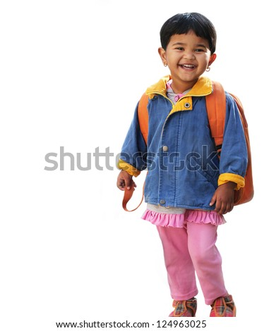 Pretty little indian pre-school girl ready to go to school in very cheerful and happy mood wearing colorful dress with a backpack. The photo is isolated on white.