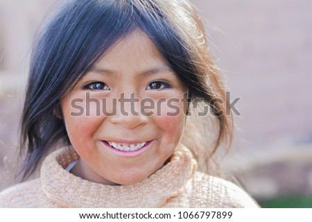 Pretty little latin girl smiling happily outside.