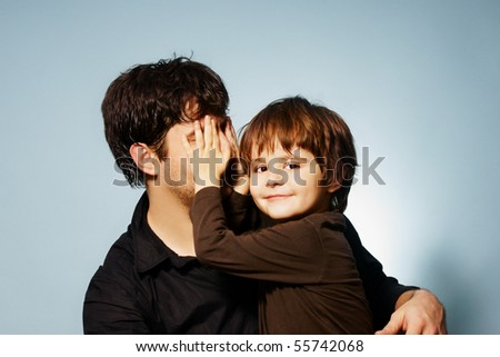 Pretty little smiling boy playing hide-and-seek with his father, studio shot