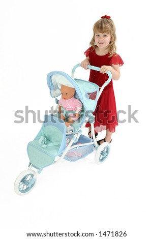 Pretty little 5 year old girl pushing baby doll in stroller.