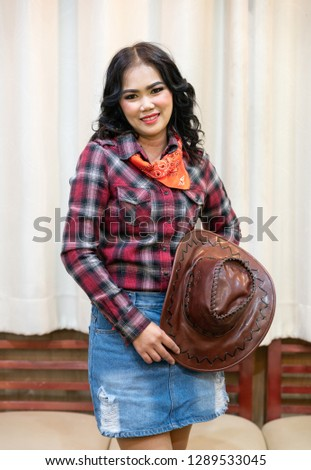 Pretty long black hair asian woman wearing plaid shirt with cowboy bandana and cowboy hat on Curtain background. attractive cowgirl in checkered shirt with  leather hat with blank space.