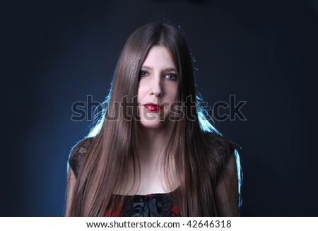 Pretty long haired brunette woman with dramatic in studio lighting, she's wearing red lipstick #42646318
