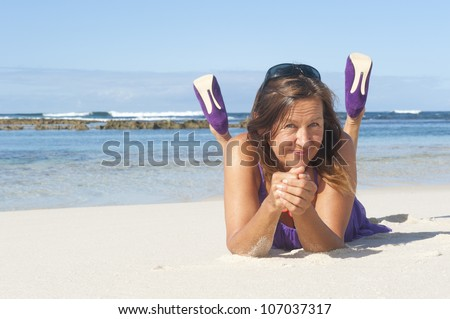 Pretty looking mature woman in sexy purple dress and high heel shoes at the beach, with ocean and blue sky as background and copy space.