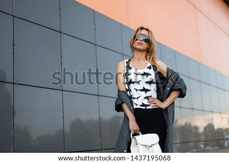 Pretty luxury young red-haired hipster woman in trendy sunglasses in trendy clothes poses in a city near a modern building. American girl fashion model on a walk on a summer day. Street style. #1437195068