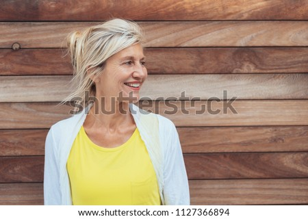 Pretty mature blond woman with a happy smile standing against a natural wood wall looking towards blank copy space