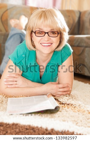Pretty mature lady lying on carpet smiling  and reading magazine