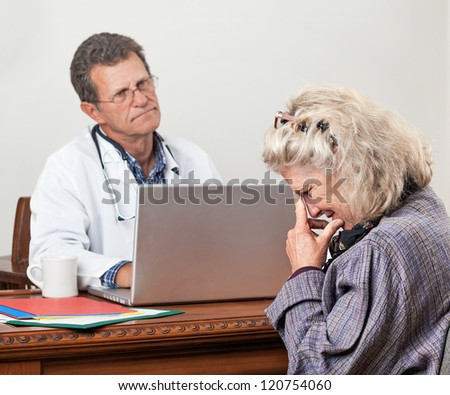 Pretty mature woman consults with her doctor in his office. Focus is on the woman'??s face. She looks worried and tearful. The doctor looks bored and impatient.